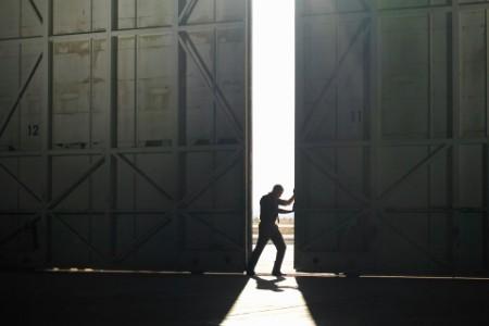 Man pushing open hangar door