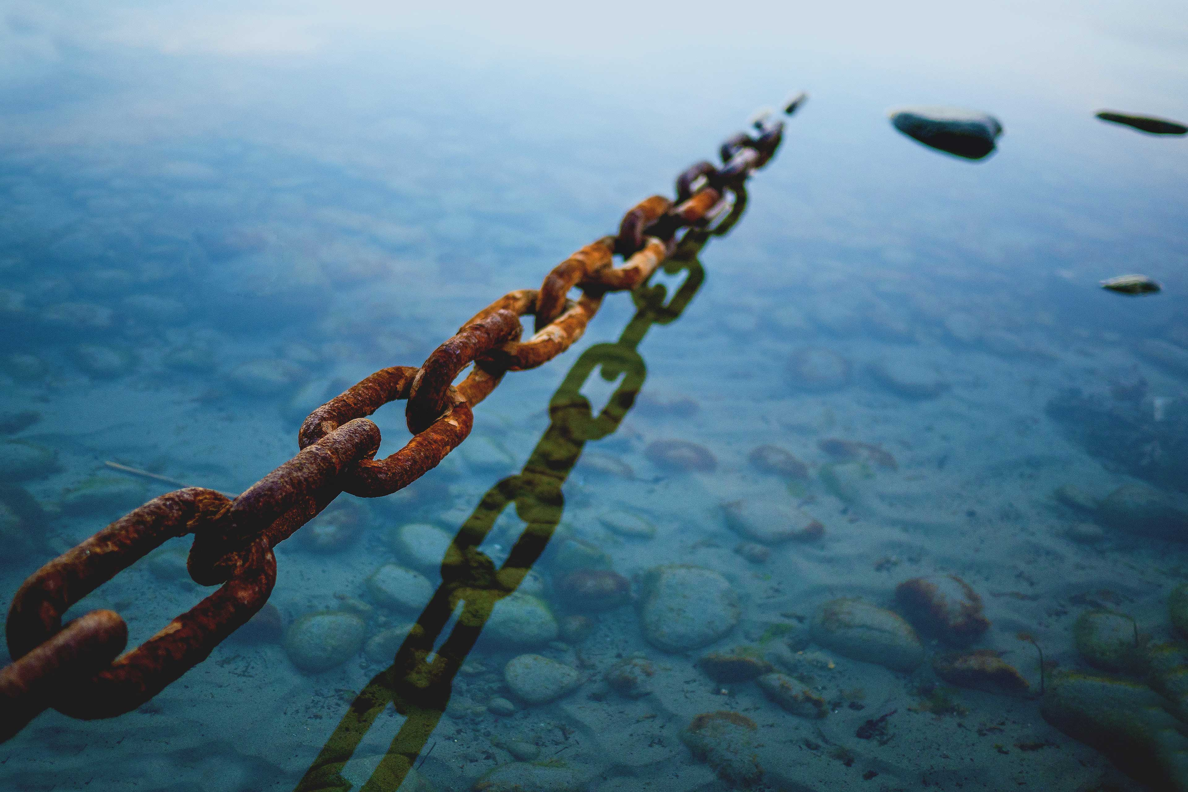 EY - Rusted chain anchored in the ocean