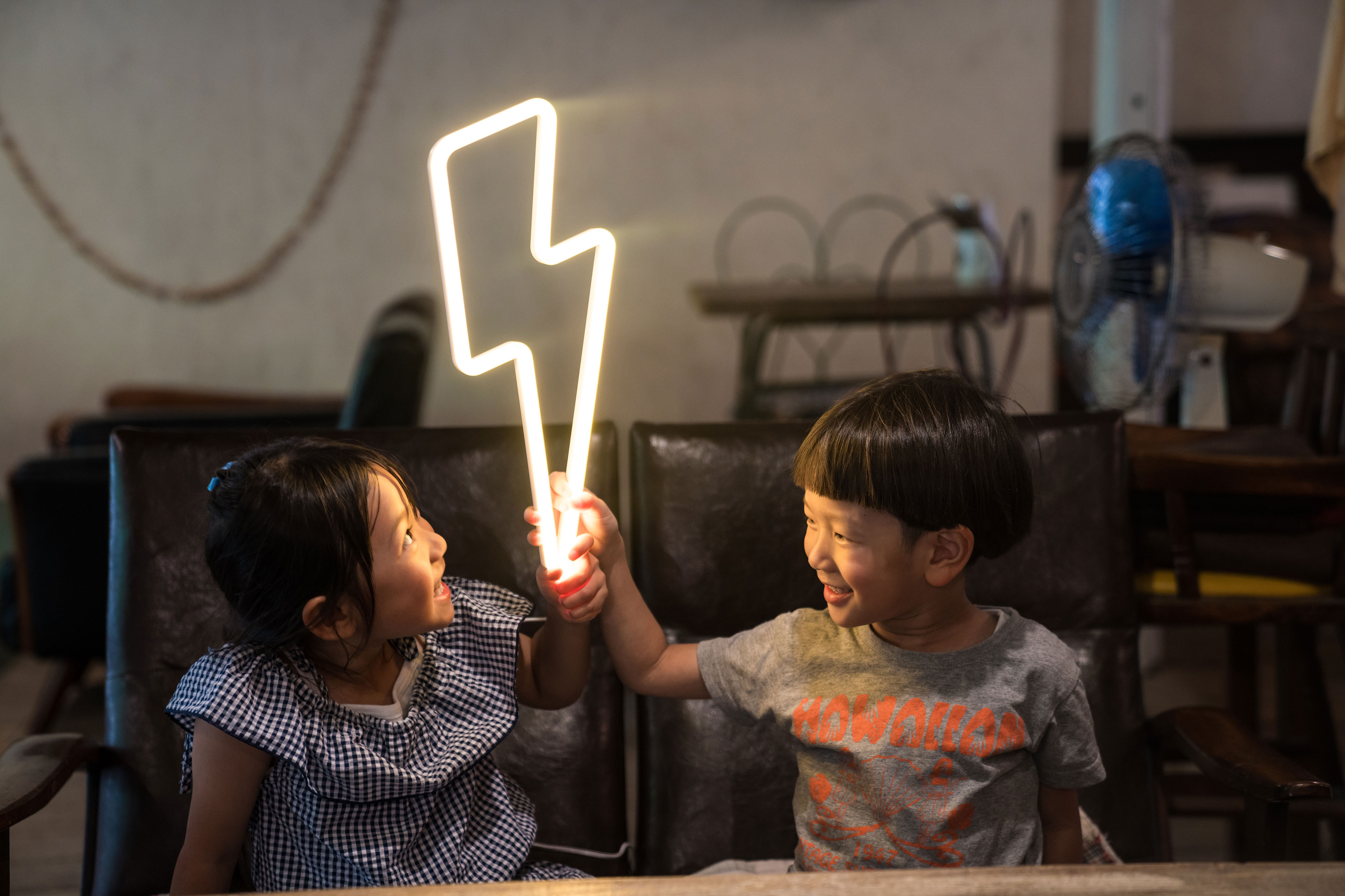 EY - Two small children with lightning bolt neon light