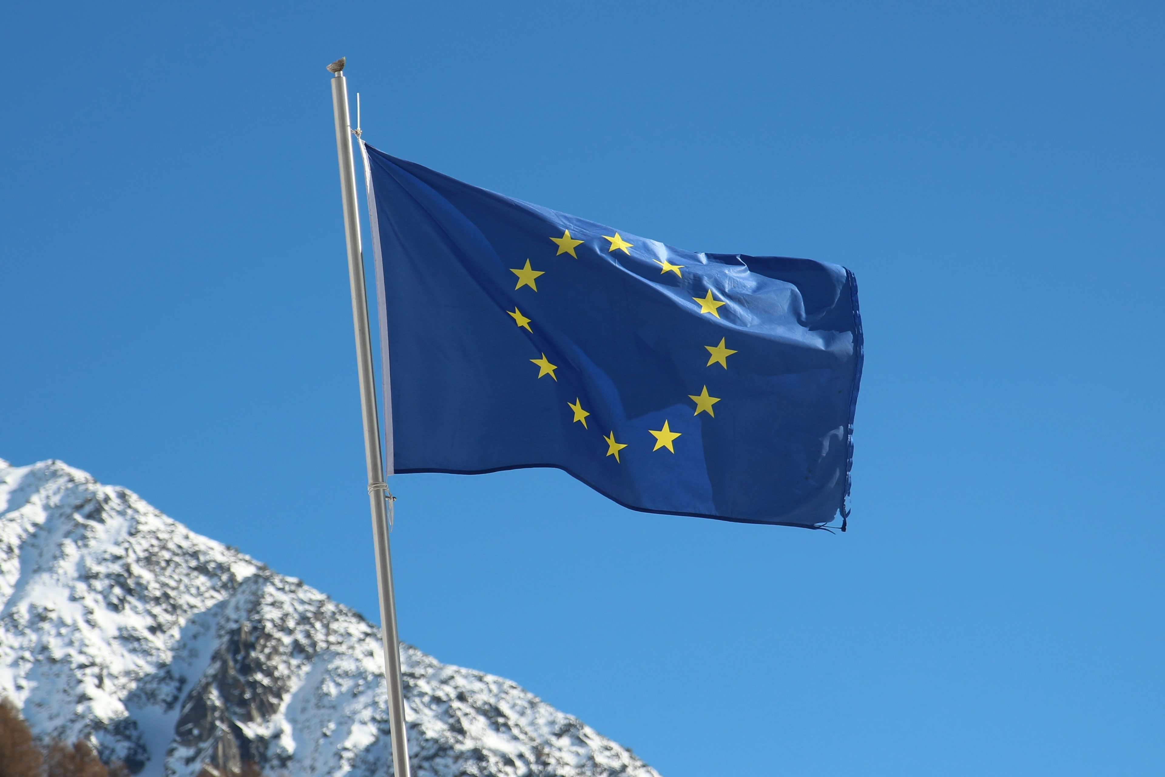 EU flag against snowy mountains
