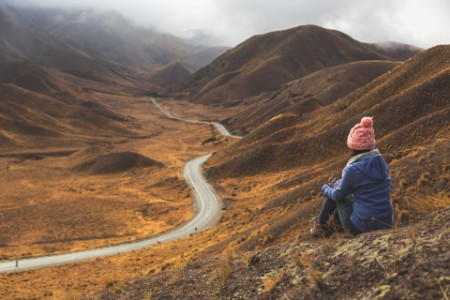 Woman sitting on hillside wearing a pick bobble hat, overlooking a road
