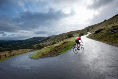 A cyclist riding uphill in a beautiful landscape