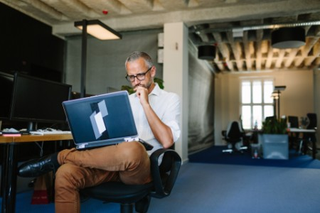 ey businessman busy working on laptop