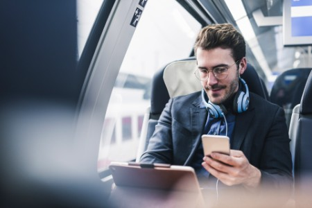EY Man on train using tablet and phone