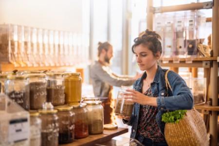 EY Lady holding jar in bulk store
