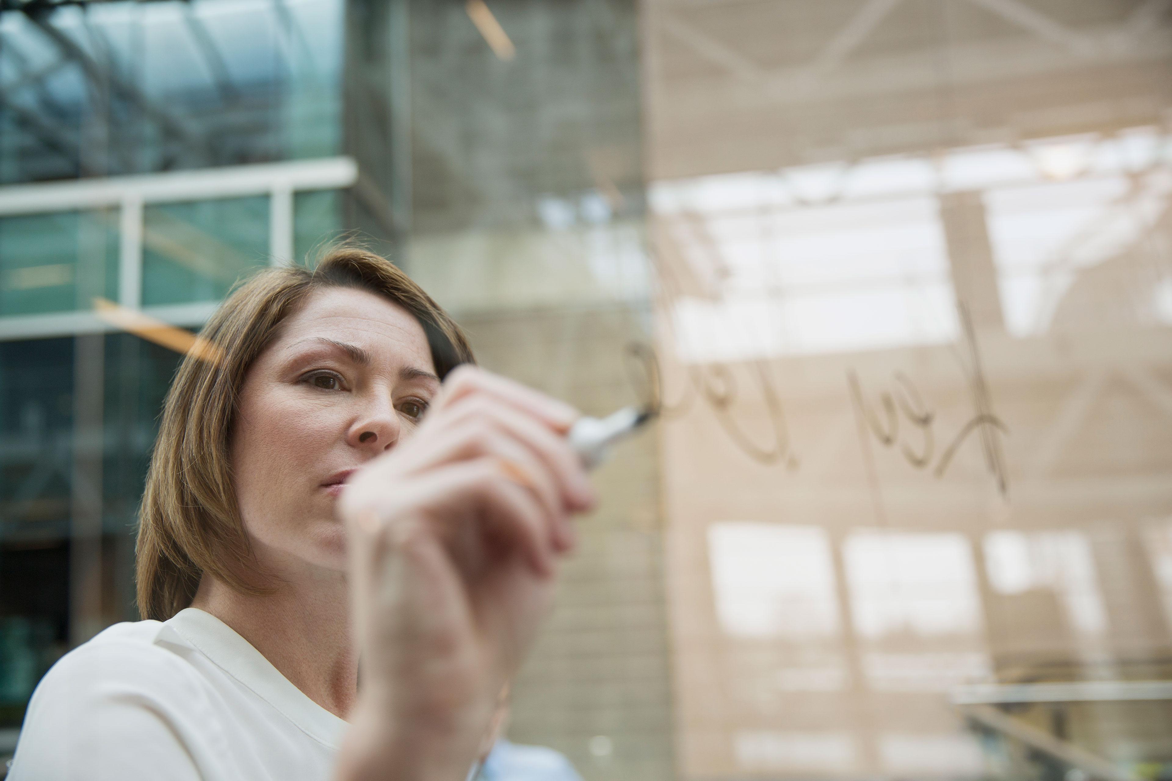 EY - Businesswoman writing on glass board