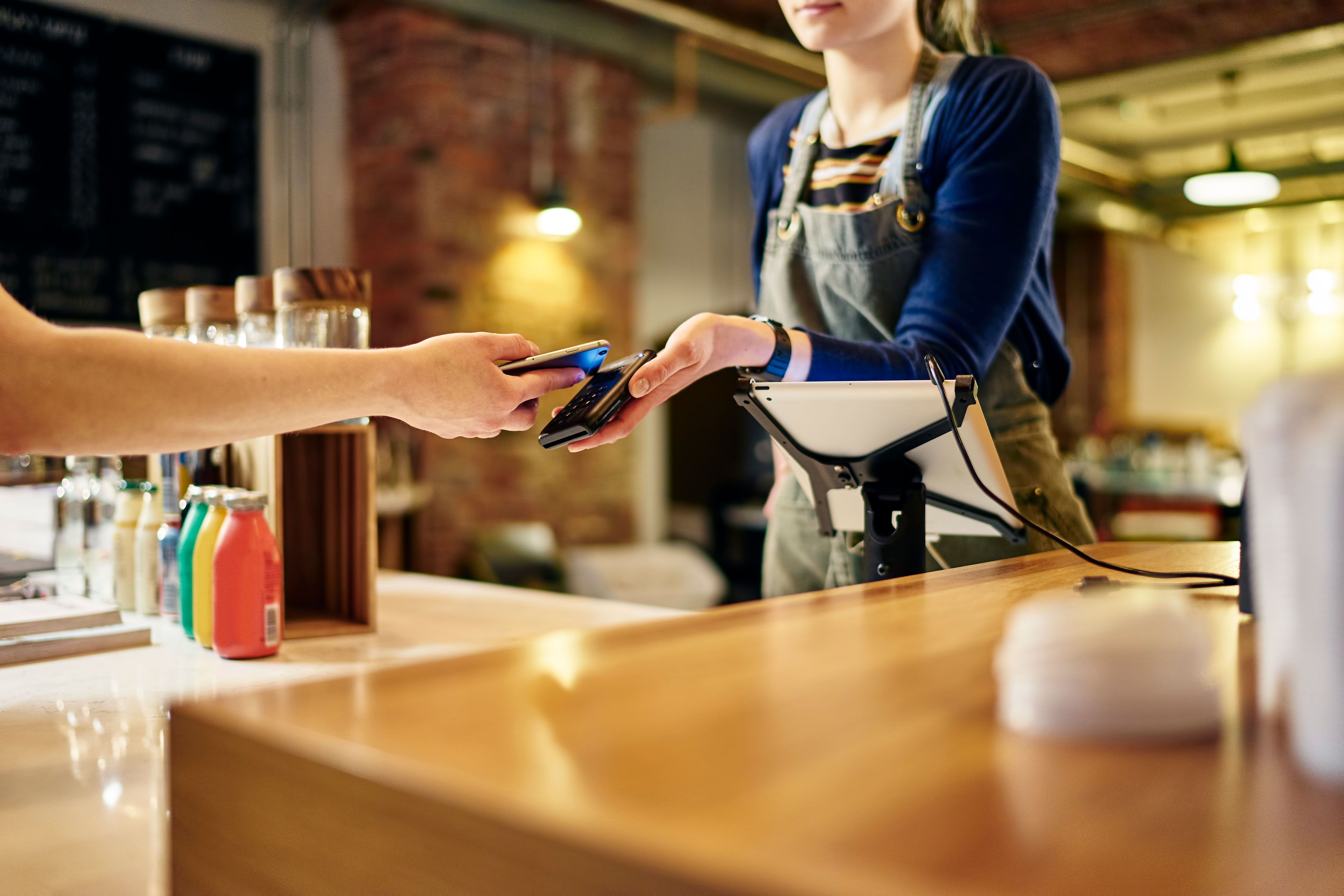 EY - Female barista taking smartphone payment