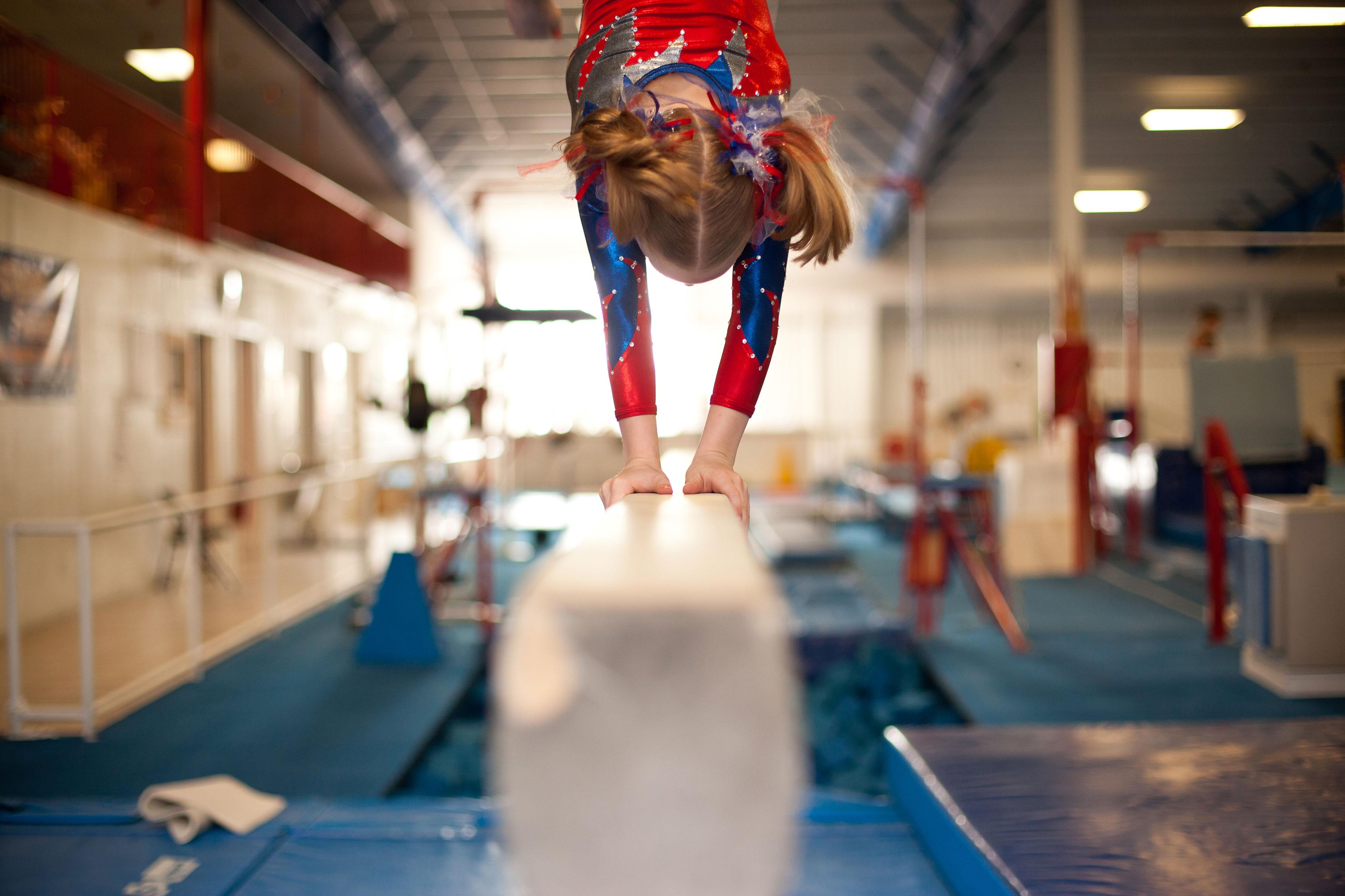 EY - Young girl gymnast doing handstand on balance beam