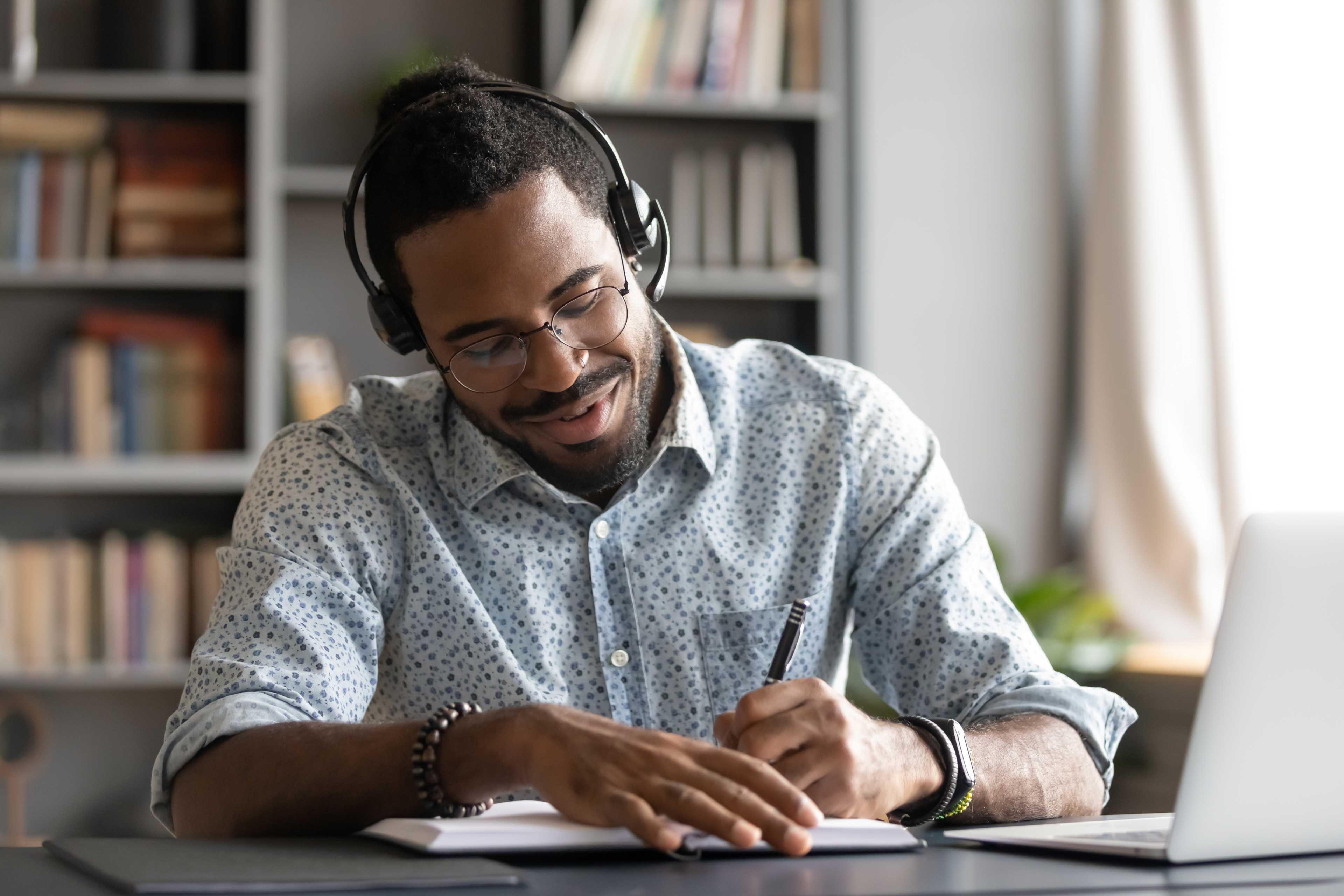 EY - Man with headphones writing notes