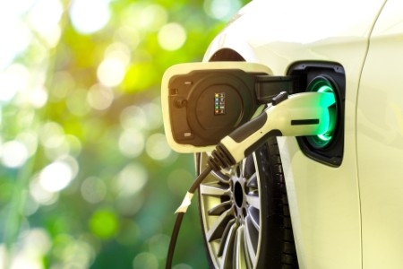 Electric car at charging station with the power cable