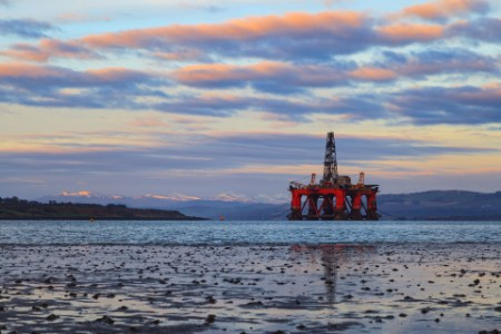 Oil rig platform in the river near the mountain