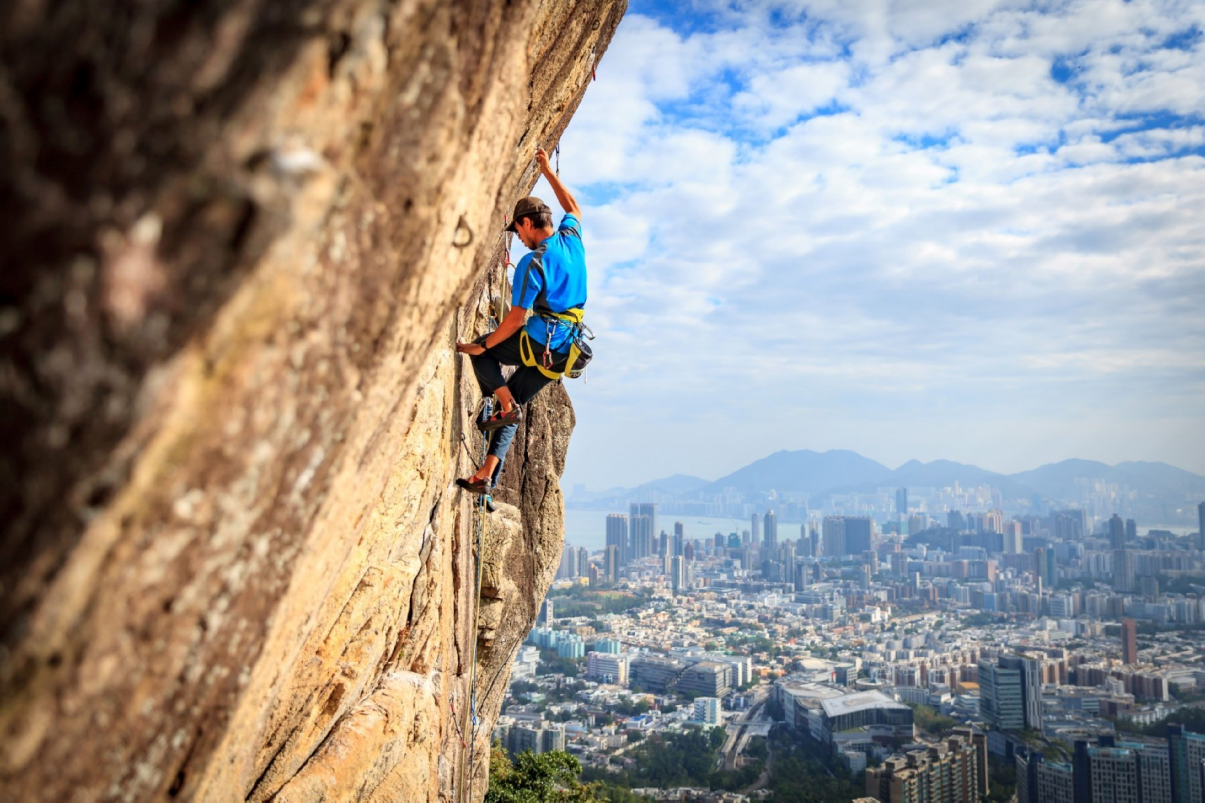 EY - Climber in a blue shirt scaling a rock face with a view of a city in the distance