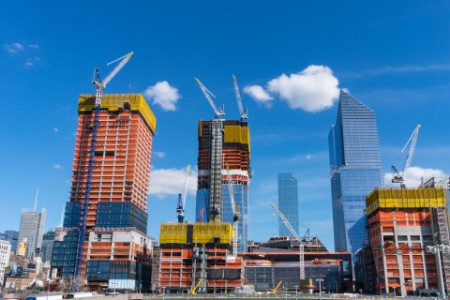 Many construction cranes work on the growing structures