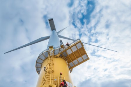Upward looking view of workers on a yellow wind turbine