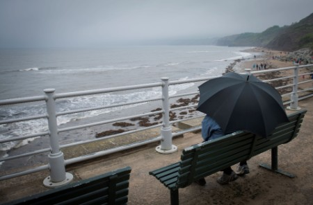 couple-sat-under-an-umbrella-by-the-sea