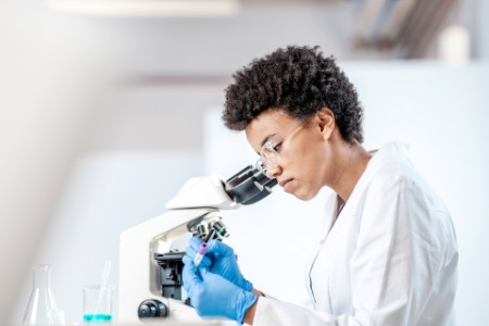 female-laboratory-worker-looking-down-microscope