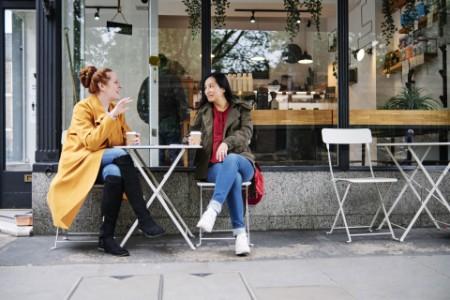 women-chatting-outside-coffee-shop