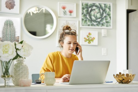 woman-working-at-home-on-laptop-and-phone