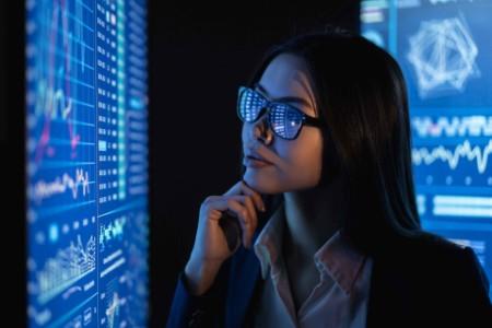 Woman looking at a wall of graphs