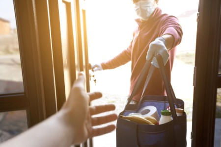 Delivery man hands over bag from grocery shop