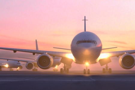 Airplanes taxiing on runway at sunset