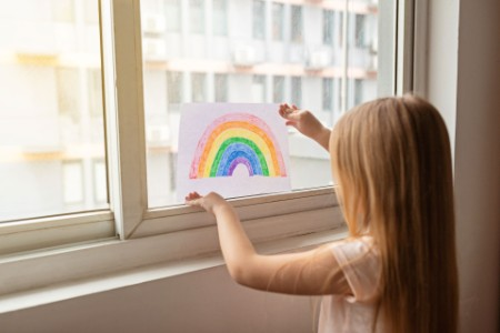Kid painting rainbow during COVID-19 pandemic
