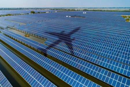 Aeroplane flying over solar panels