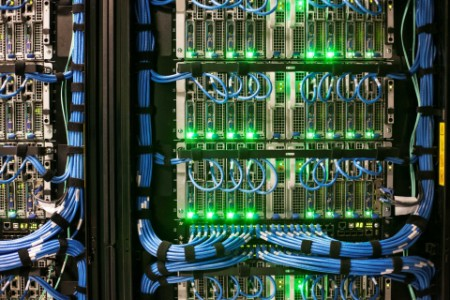 view of a server with numerous connections, blue wire and green lights