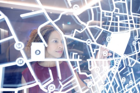 Woman looking at a glass panel, showing a street map