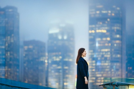 Woman in a black coat, with skyscrapers in the background