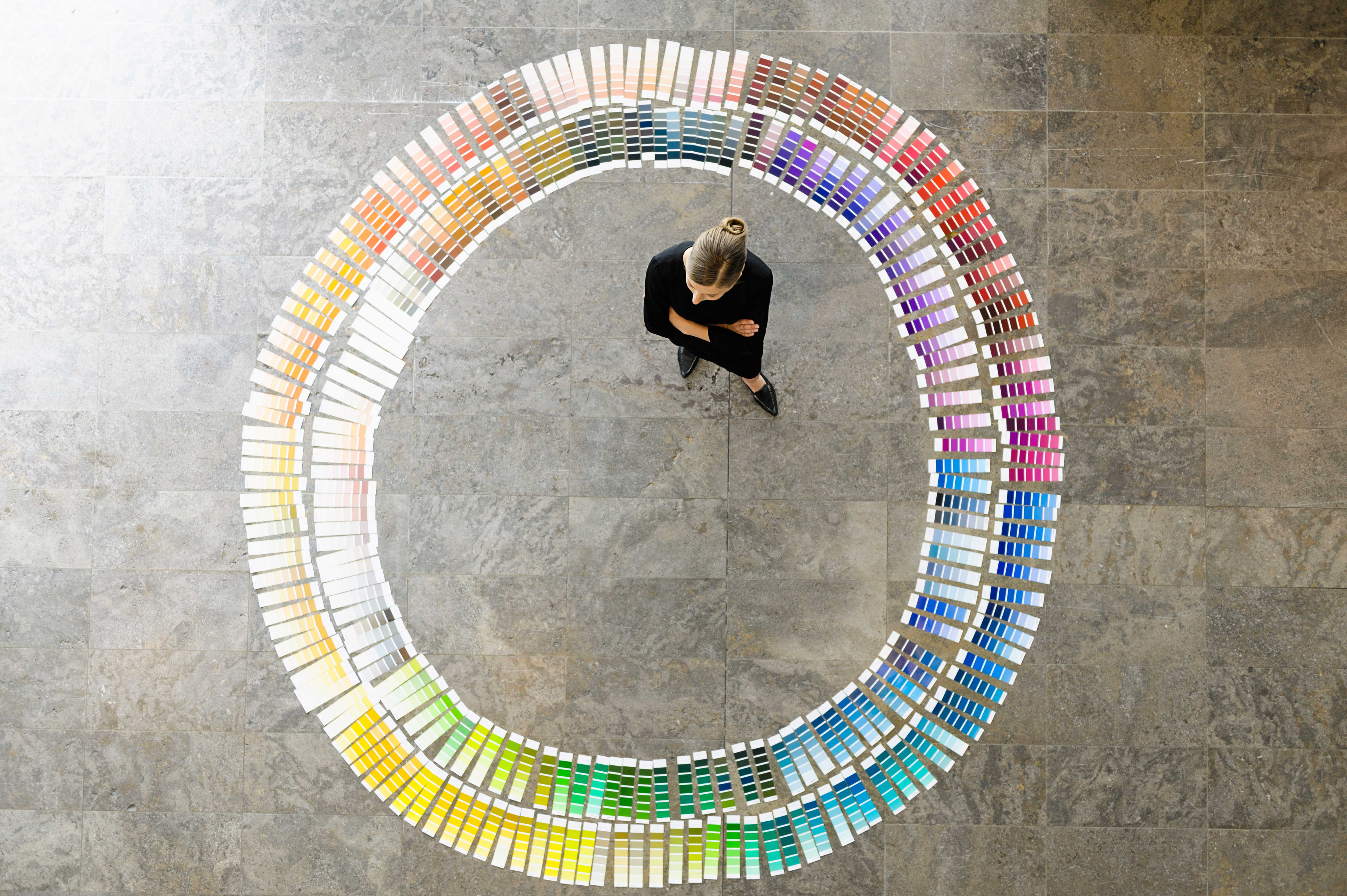 EY - Businesswoman standing in circle of colour swatches
