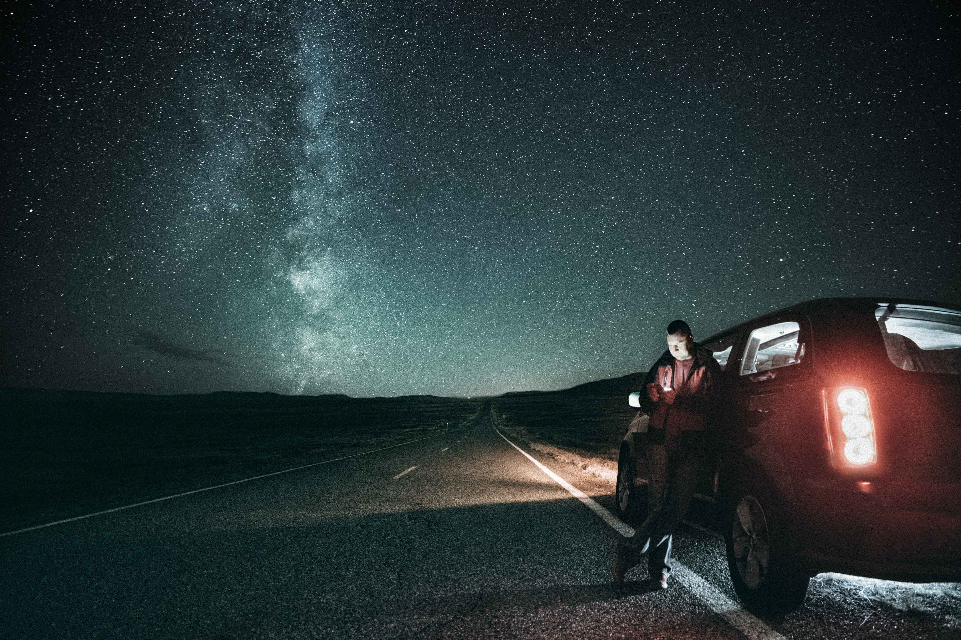 EY - Man and car against Milky Way