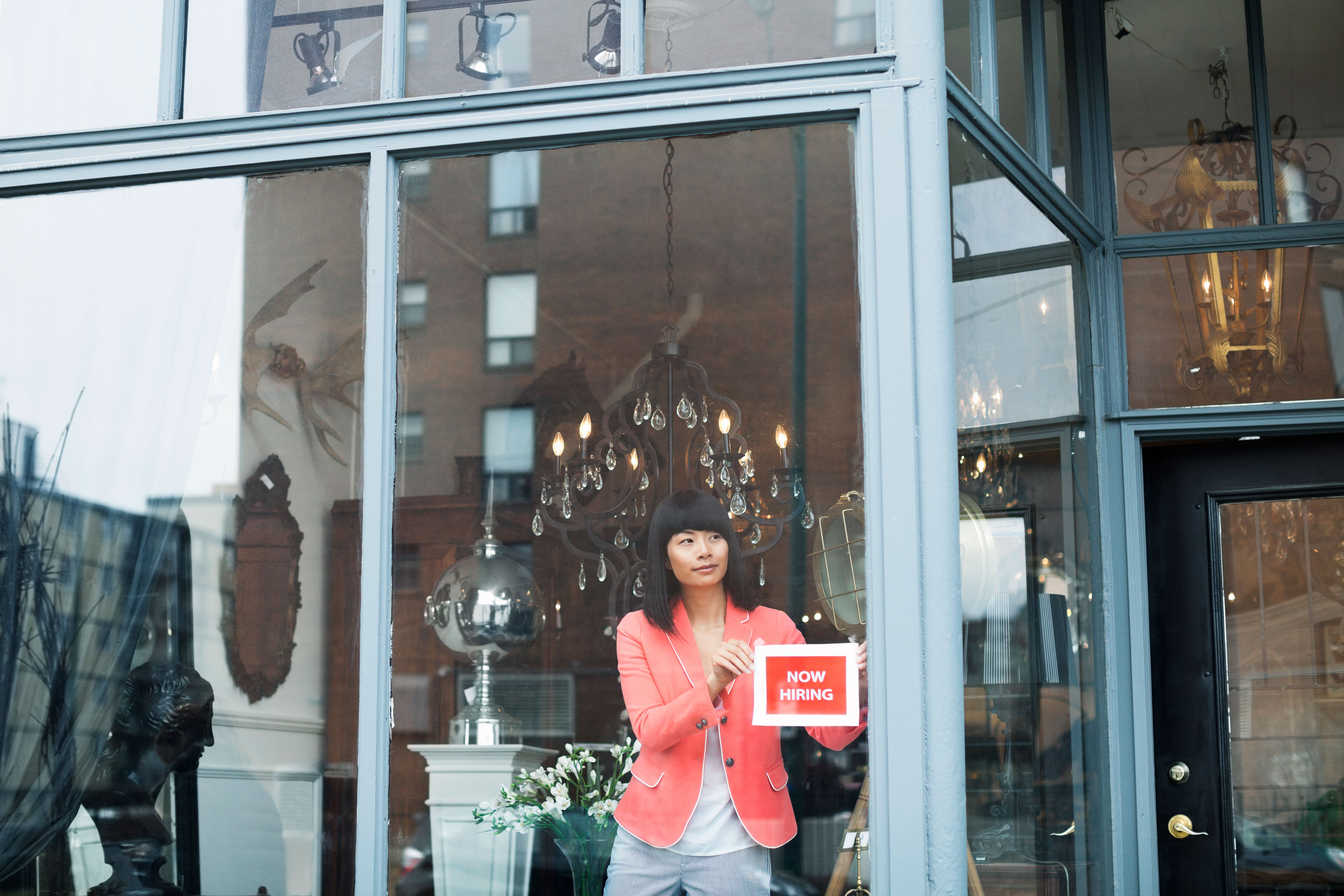 EY - Woman displaying help wanted sign in furniture store window