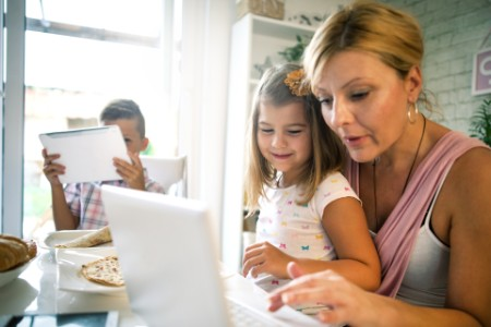 Woman with a child working on a laptop computer