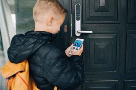 Boy using smartphone to unlock front door