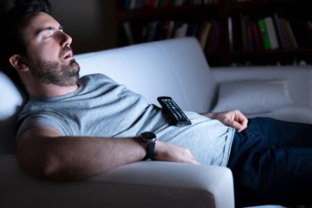 Man sleeping holding a TV remote.