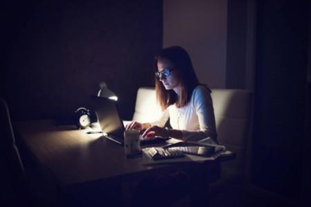Women working in laptop at late night in dark