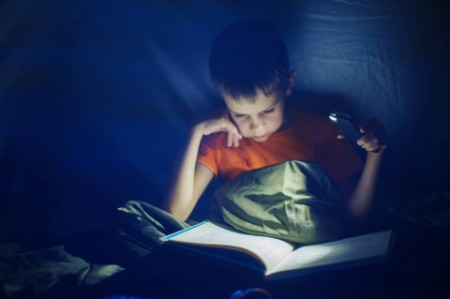 Small kid using a mobile torch to read a book