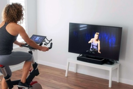 Woman on exercise bike, participating in an online class