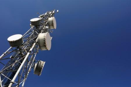 Network telecoms mast against blue sky