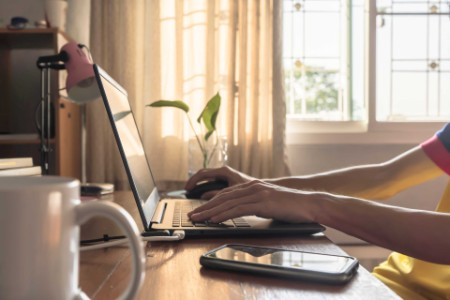 Side view of a person working from home on a laptop