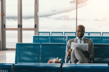 EY - Businessman reading a newspaper, in an airport lounge