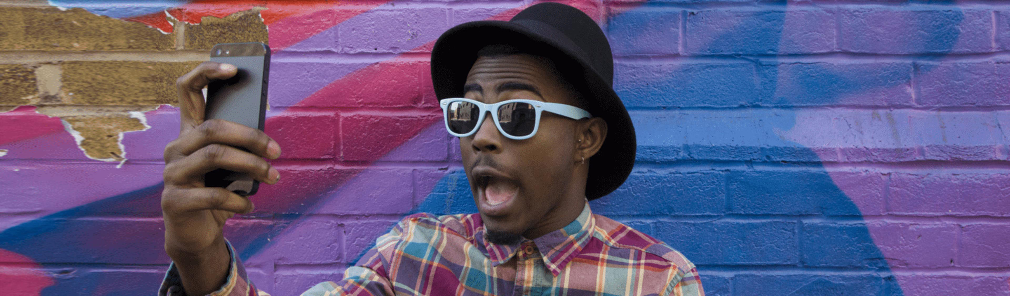 EY - Black man taking selfie near colorful wall