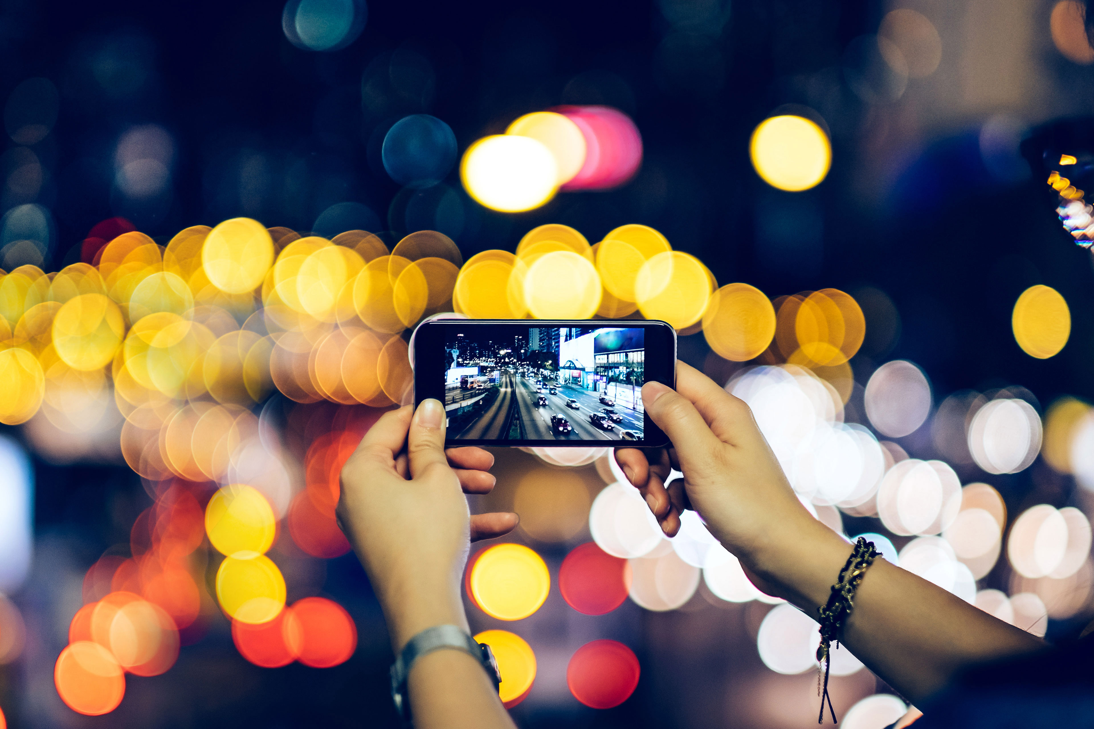 Woman photographing night scene with smartphone