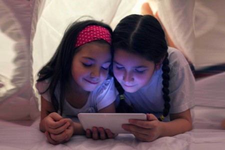 Sisters using digital tablet in bed