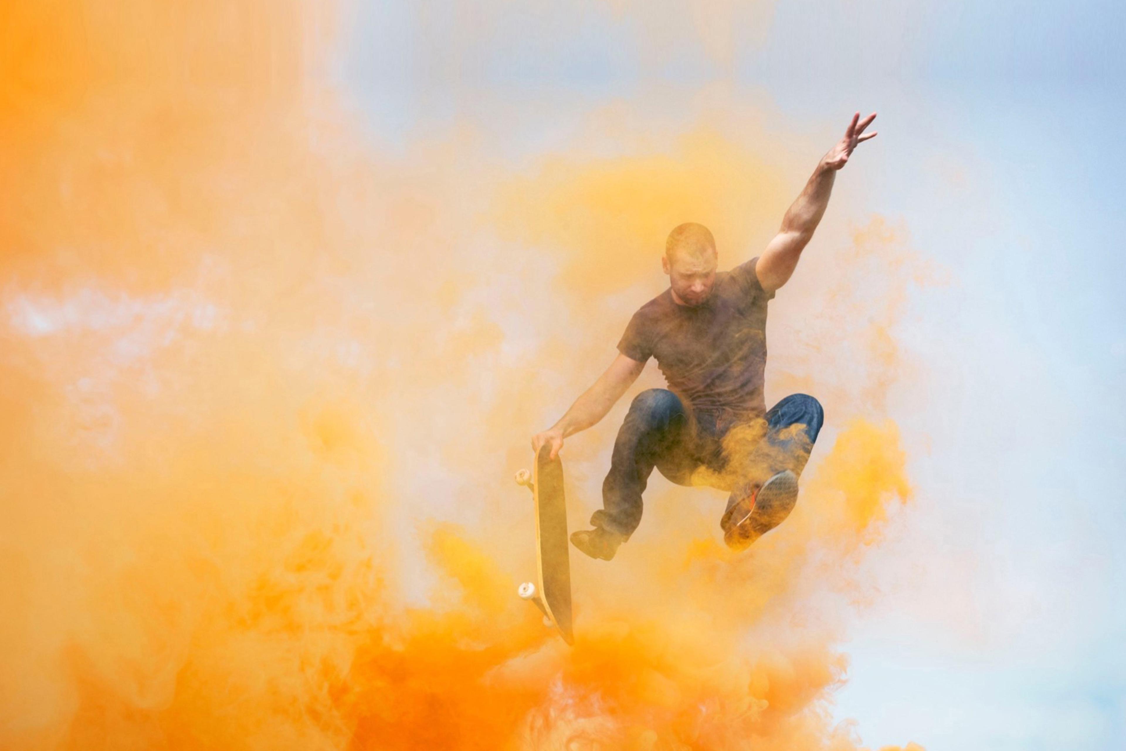 EY - Man jumping through orange smoke with skateboard