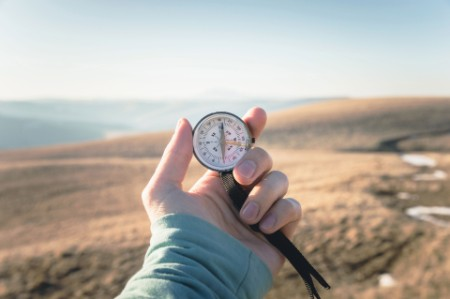 ey person holding a compass
