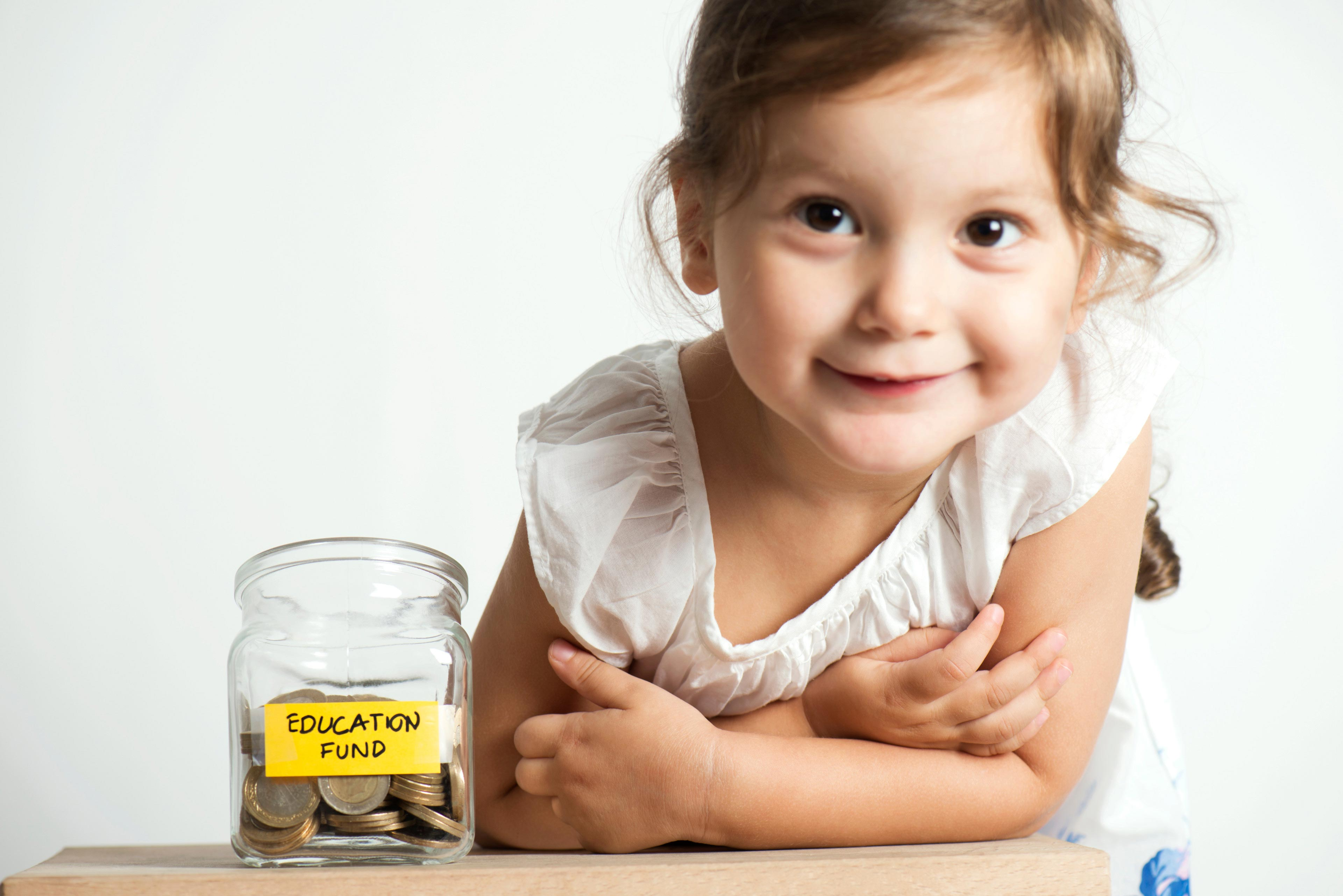 Little girl with coins in glass money jar with education fund label