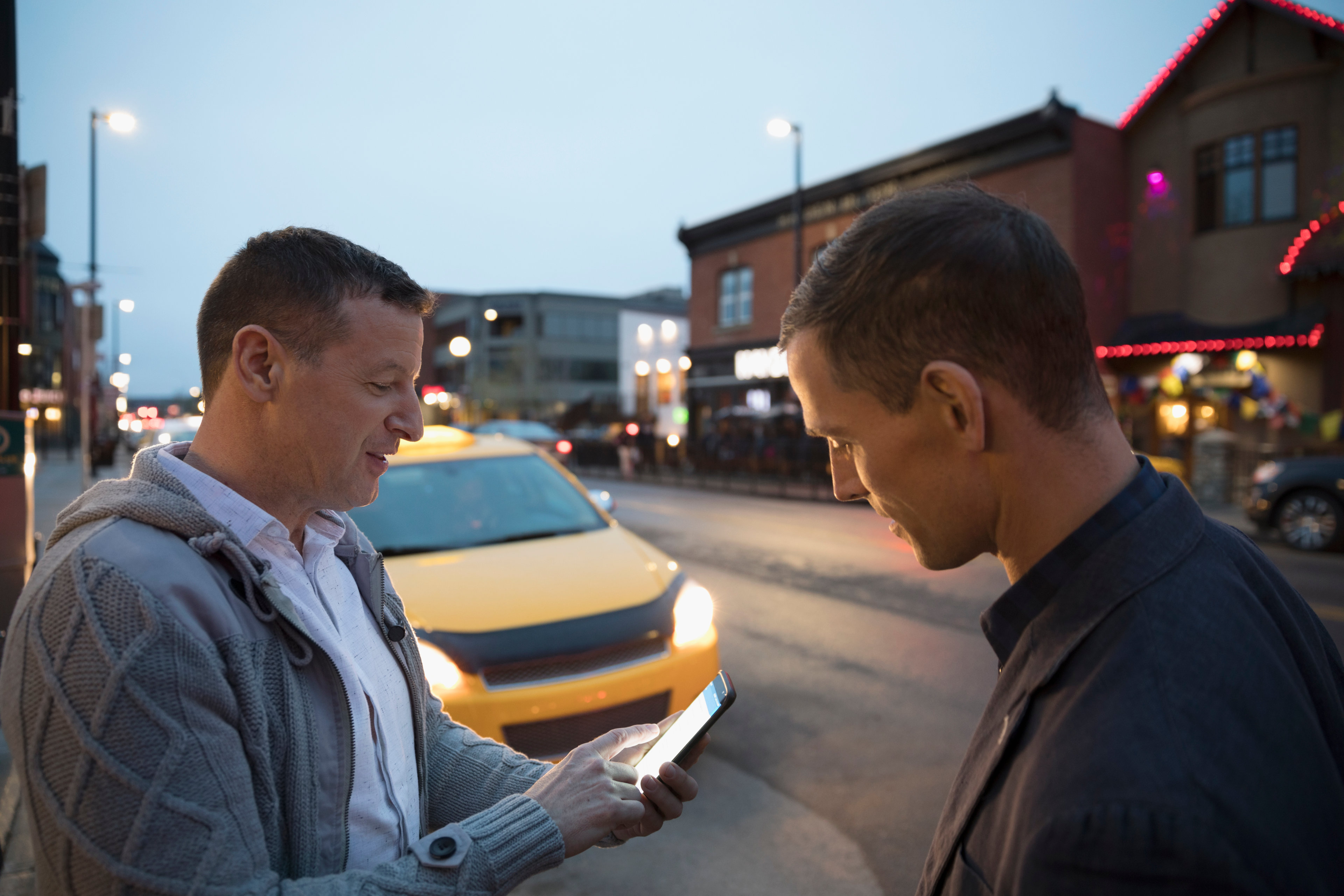 Men using smartphone for crowdsourced taxi on urban street at night