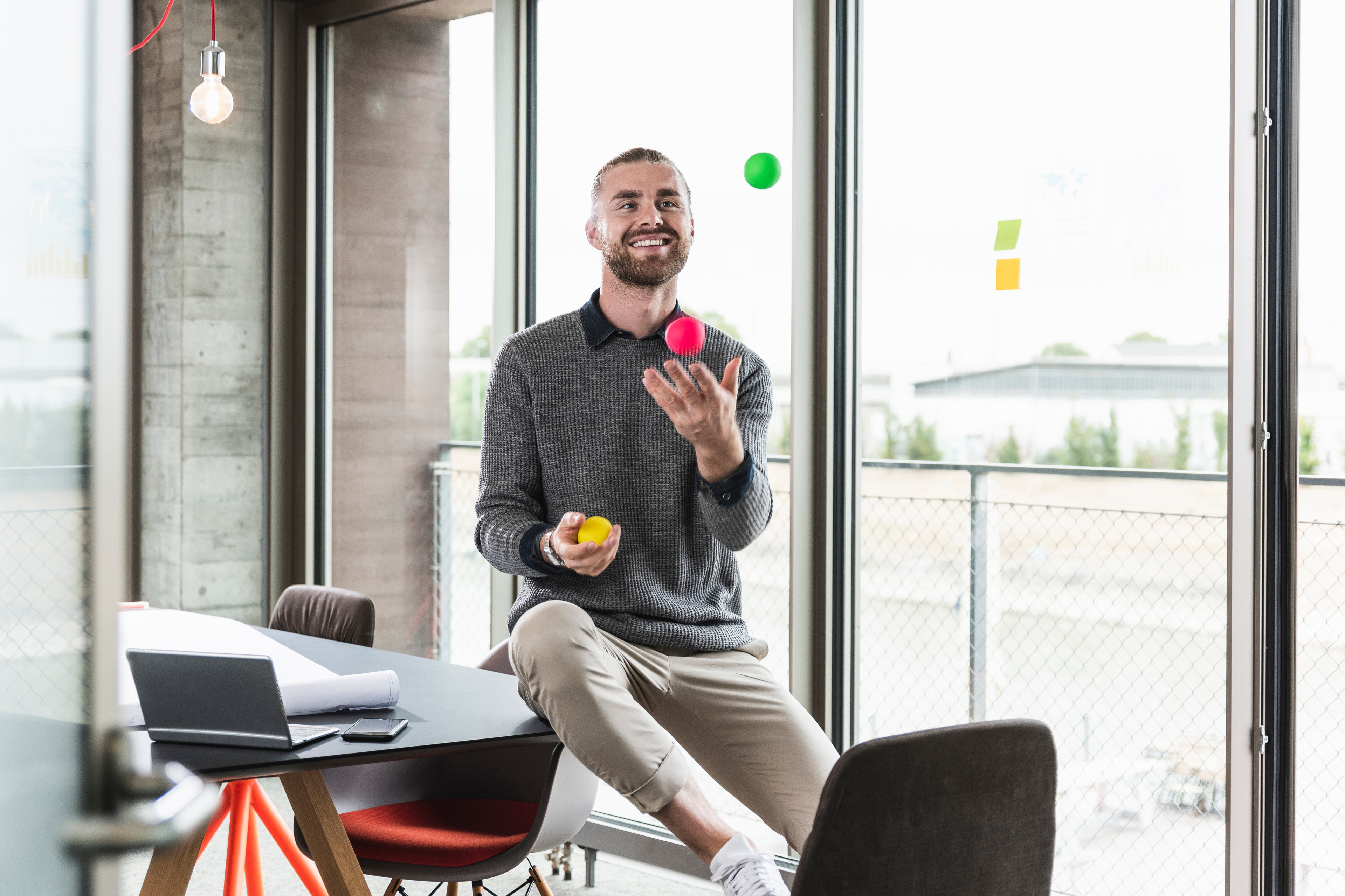 Smiling businessman juggling with balls